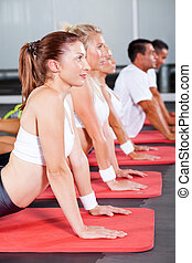 group of fitness people stretching on gym floor