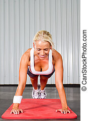 young fitness woman doing push ups