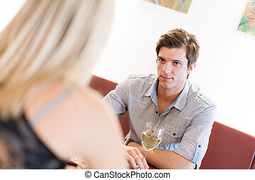 Young man looking at a woman on date