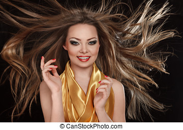 Young smiling woman with long hair fluttering under wind
