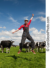 Happy farmer in field with cows - Happy young farmer jumping...