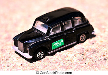 London Transportation - A Black Taxi isolated over tar-seal.