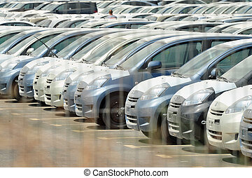 New Cars Importing - Rows of new cars in import parking lot.