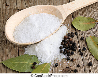 Salt in spoon on wooden background