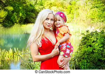 Young mother with smiling pretty child, outside portrait