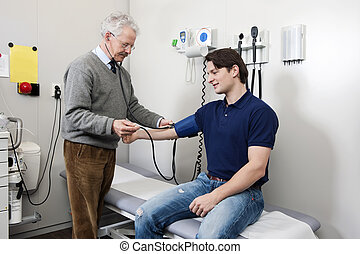 Blood pressure - Friendly doctor taking a blood pressure...