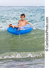 Boy with inflatable rides around on the waves summer sea