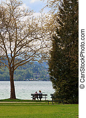 Two people on a bench - Two people sitting on a bench,...