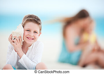 Cute boy with seashell at the beach with his family on...
