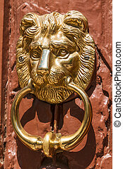 lionhead knocker found on a door of a classical mansion in...