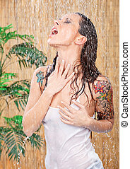 woman with tattoos under shower - young woman with tattoos...