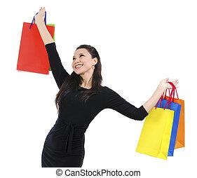 Happy shopper holding shopping bag high isolated on white...
