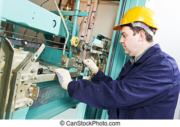 machinist with spanner adjusting lift mechanism - One...