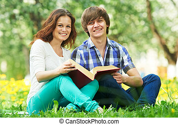 two smiling young students outdoors with book