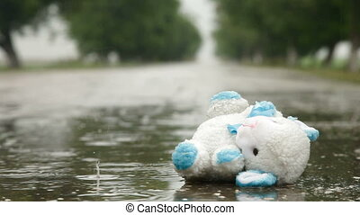Lost Toy In A Puddle Under Rain