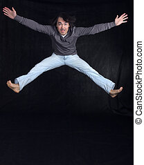 Young man jumping, over black background - Young handsome...