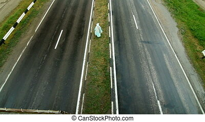 Road Divider - The man goes on dividing line of the road,...