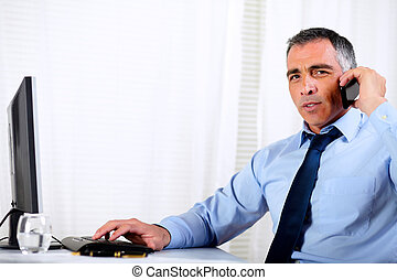 Hispanic professional man conversing on mobile - Portrait of...
