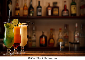 Three tropical mixed drinks, shot in bar with space for copy...