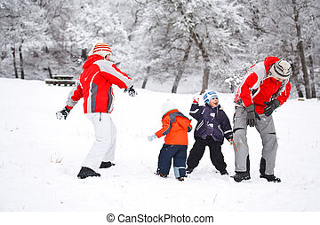 Family having fun in snow - Family having snowball fight in...