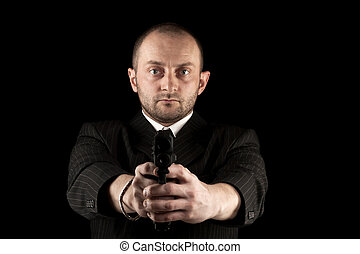 Gunman ready to shoot, isolated on black