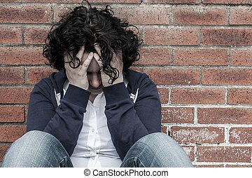 jovem, desesperado, mulher, sentando, contra, parede