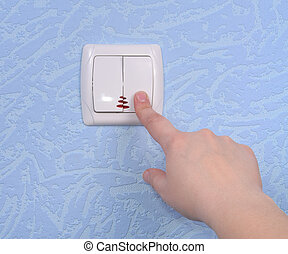 Hand pressed to switch on the wall