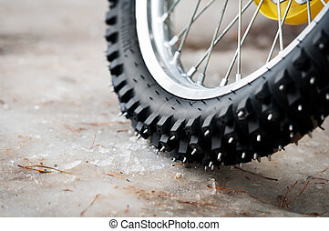 Tyre of motocross bike on ice and snow on background,...