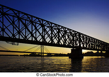 Bridge at sunset - An old bridge construction silhouette at...