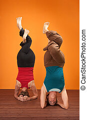 Women In Headstand Posture - Two fit women in upside down...