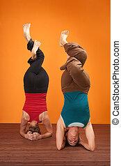Women In Headstand Posture - Two fit women in upside down...
