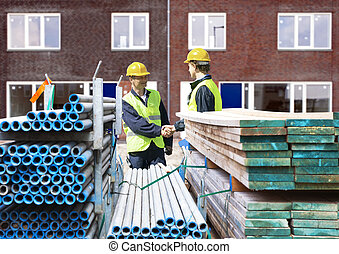 Building contractors - Two building contractors shaking...