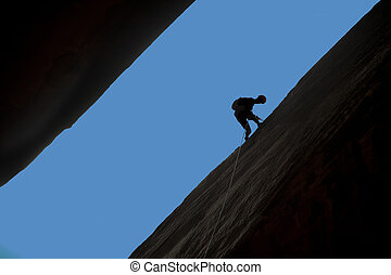 Silhouette of rock climber rappelling a crack with blue sky...