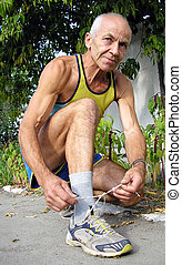 Active senior - An elderly man in a T-shirt and athletic...