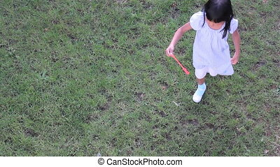 Asian Girl Looks Up Making Bubbles - A cute Asian girl spins...