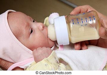 porridge - The little girl eats porridge from a bottle