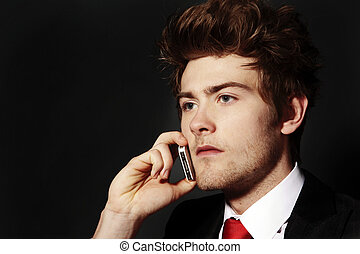 making a call - low key image of young man on his mobile...