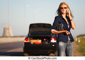 Young woman with a broken car calling for help