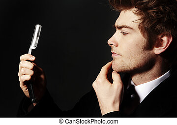 cut throat razor - low key image of a young man holding a...