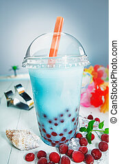 Colourful healthy boba or bubble tea with red berries served...