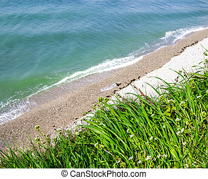 Beautiful sea ??view from the cliff with green grass and flo