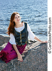 Medieval woman near the sea - Medieval woman sitting on a...