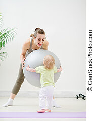 Mom and baby playing with fitness ball