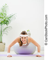 Fitness woman making push up on fitness ball