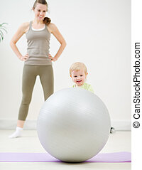 Mother and kid playing with fitness ball