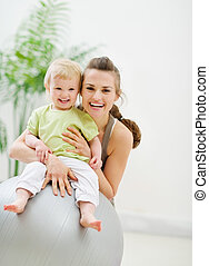 Portrait of happy mother and baby in gym