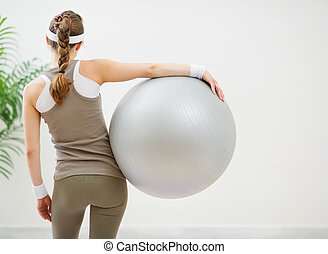 Athletic woman with fitness ball standing back to camera