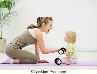Baby helping mother lifting dumb-bells
