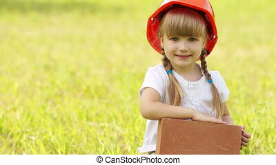 Little girl with the red brick buil - A little builder