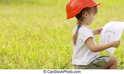 Little girl builder in the meadow
